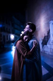 Elegante frau, die mit jungem mann auf promenade nachts umarmt