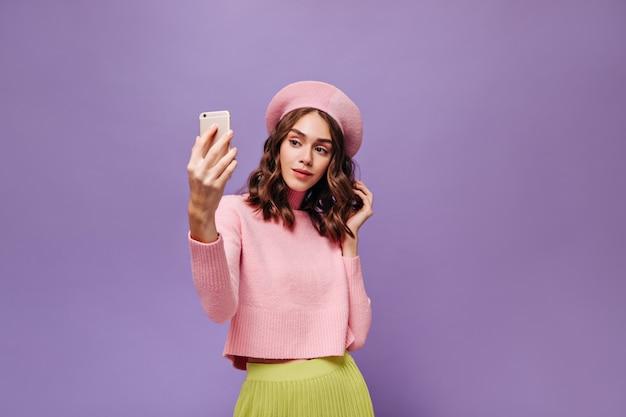 Elegante frau hält telefon und macht selfie