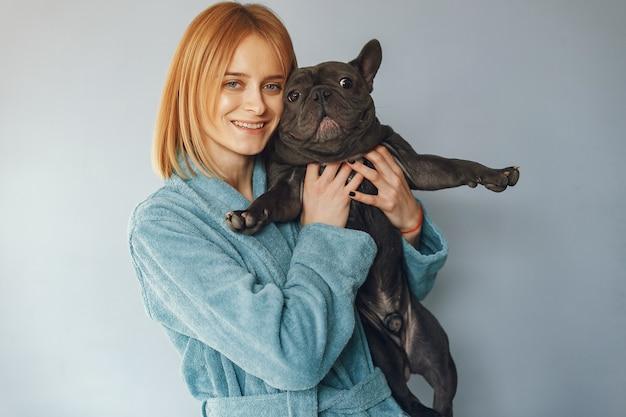 Elegante frau im blauen bademantel mit schwarzer bulldogge