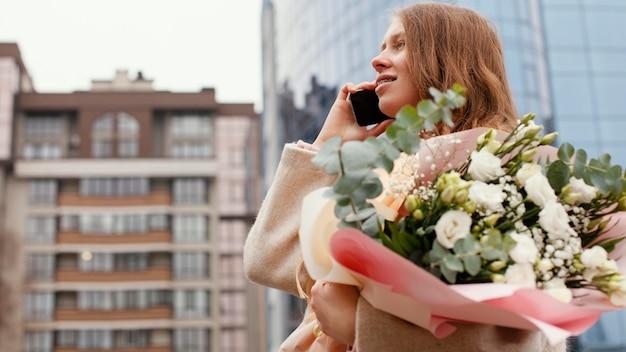 Elegante frau im freien, die am telefon spricht und blumenstrauß hält