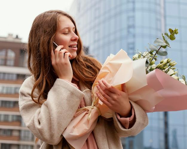 Elegante frau im freien, die am telefon unterhält und blumenstrauß hält
