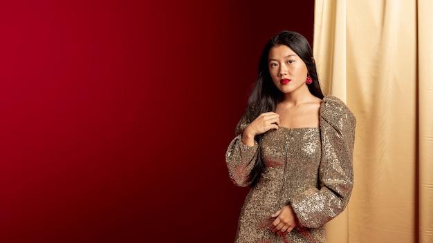 Elegante frau im kleid, das für chinesisches neues jahr aufwirft