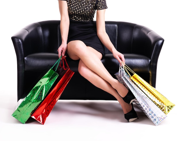 Elegante frau im schwarzen kleid mit einkaufstüten, die auf der couch lokalisiert auf weißer wand sitzen.