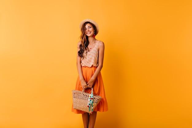 Elegante frau im sommeroutfit bereitet sich auf urlaub vor. romantisches ingwermädchen im strohhut, der auf orange mit tasche aufwirft.
