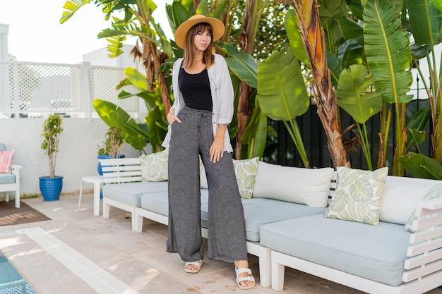 Elegante frau im strohhut, die im gemütlichen tropischen resort nahe pool aufwirft