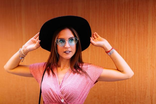 Elegante frau im zufälligen rosa kleid, in der denimjacke und in der katzensonnenbrille des blauen auges, die ihren hut berührt und ruhig und überzeugt schaut. vintage, bunte und orange wand