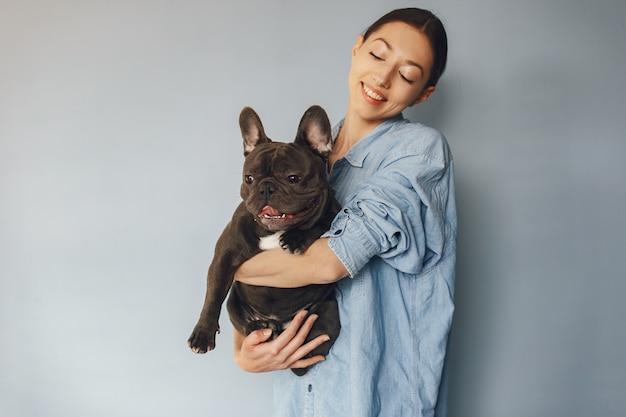 Elegante frau in einem blauen hemd mit schwarzer bulldogge