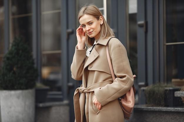 Elegante frau in einem braunen mantel in einer frühlingsstadt