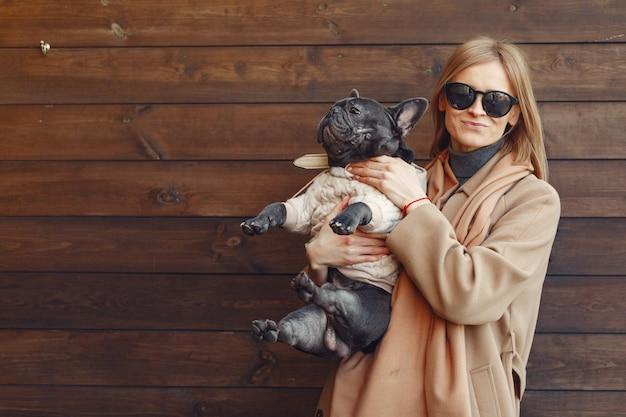 Elegante frau in einem braunen mantel mit schwarzer bulldogge