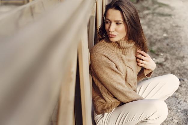 Elegante frau in einem braunen pullover in einer frühlingsstadt