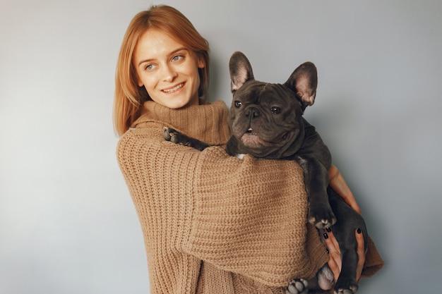 Elegante frau in einem braunen pullover mit schwarzer bulldogge