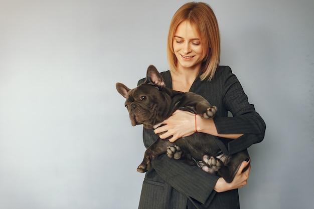 Elegante frau in einem schwarzen anzug mit schwarzer bulldogge