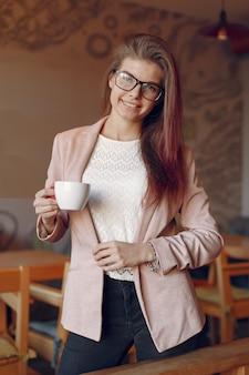 Elegante frau in einer rosa jacke, die zeit in einem café verbringt