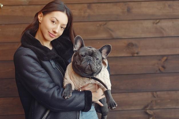 Elegante frau in einer schwarzen jacke mit schwarzer bulldogge