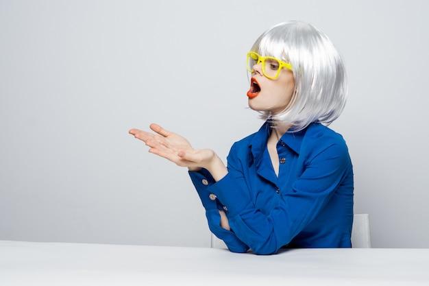 Elegante frau in einer weißen perücke sitzt an einem tisch in gelben gläsern und gestikuliert mit ihren handgefühlen