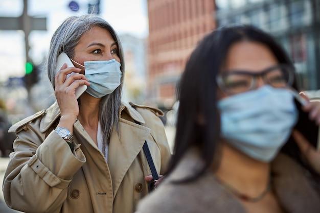 Elegante frau in medizinischer maske mit telefongespräch im freien