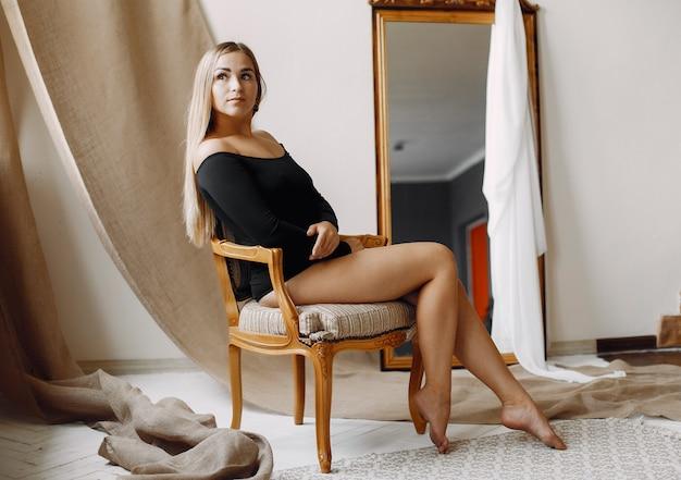 Elegante frau mit dem sitzen des blonden haares
