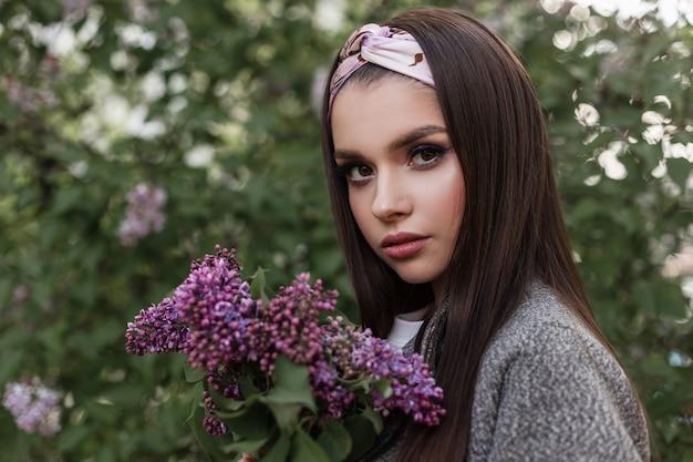 Elegante frau mit farb-make-up mit modischem bandana in stilvollem mantel mit blumenstraußflieder genießen den frühling auf grünem hintergrundlaub im park. wunderschönes mädchen des frühlingsporträts mit purpurroten blumen draußen.