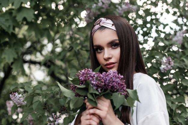 Elegante frau mit farb-make-up mit modischem bandana in weißem, stilvollem hemd mit fliederstrauß genießen den frühling auf grünem hintergrundlaub im park. wunderschönes mädchen des niedlichen porträts mit lila blumen.