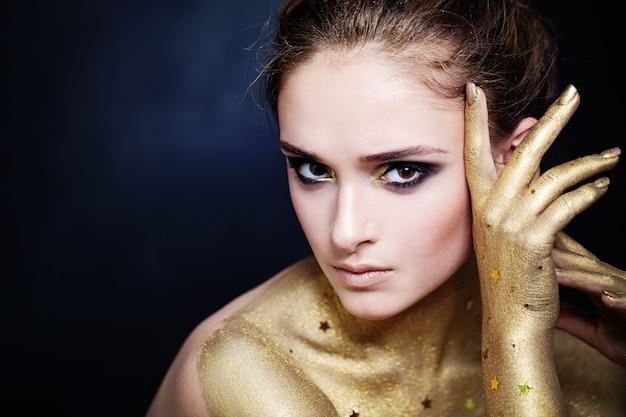 Elegante frau mit goldener haut und glamourösem party-make-up
