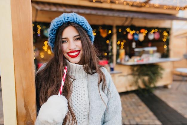 Elegante frau mit hellem make-up, das mit lutscher nahe weihnachtsmarkt am kalten tag aufwirft. erfreutes europäisches weibliches modell trägt wollmantel, der neujahrsbonbons hält und lacht.