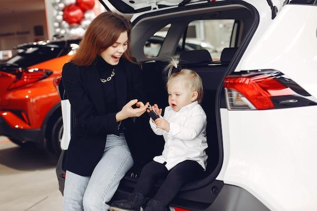 Elegante frau mit kleiner tochter in einem autosalon