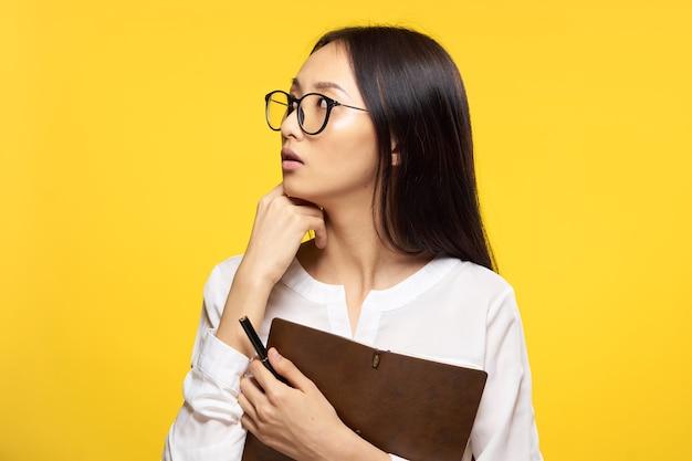 Elegante frau mit notizblock in händen offiziellen büro gelben isolierten hintergrund