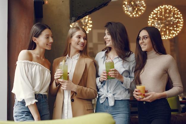 Elegante frauen, die in einem café stehen und einen cocktail trinken