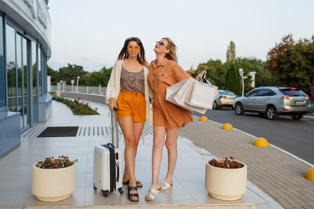 Elegante frauen nach dem verlassen der reise und dem einkaufen im freien nahe flughafen