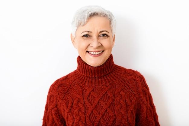Elegante fröhliche kaukasische rentnerin mit kurzer pixie-frisur, die breit lächelt, gekleidet in stilvollen gestrickten burgunderfarbenen pullover. menschen, alter, stil, strickwaren und modekonzept