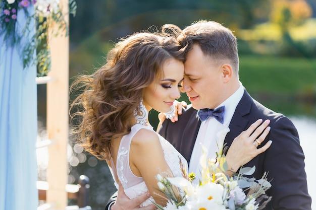 Elegante gelockte braut und glücklicher bräutigam