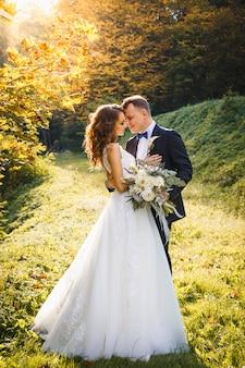 Elegante gelockte braut und stilvoller bräutigam