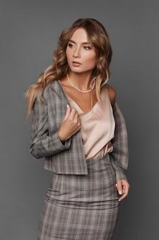 Elegante geschäftsdame im karierten anzug und in der satinbluse, die beiseite schauen und auf dem grauen hintergrund posieren, lokalisiert.