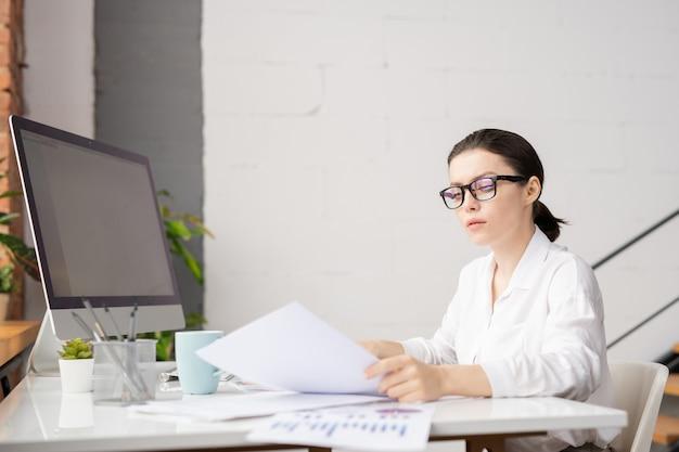 Elegante geschäftsfrau der jungen brünette in den brillen und im weißen hemd, die papiere durch schreibtisch im büro lesen