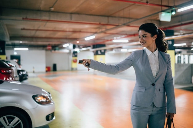 Elegante geschäftsfrau, die ihr auto mit schlüsseln in der tiefgarage abschließt.