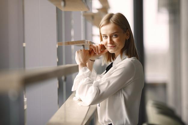 Elegante geschäftsfrau, die im büro steht