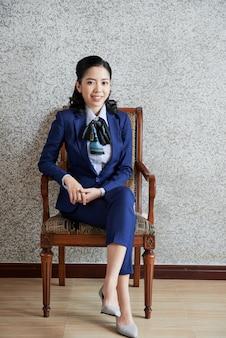 Elegante geschäftsfrau, die im lehnsessel sitzt