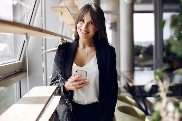 Elegante geschäftsfrau, die in einem büro arbeitet und das telefon benutzt