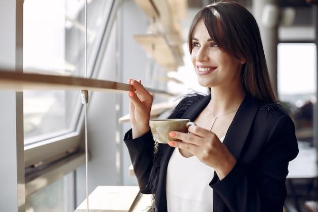 Elegante geschäftsfrau, die in einem büro arbeitet und einen kaffee trinkt