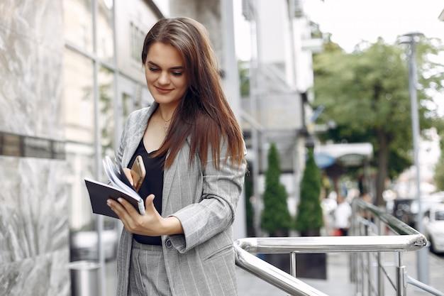 Elegante geschäftsfrau, die in einer stadt arbeitet und das notizbuch benutzt