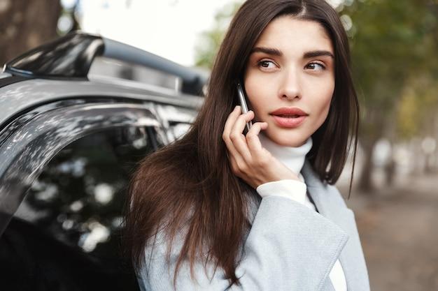 Elegante geschäftsfrau, die telefonanruf in der nähe des autos macht. f.