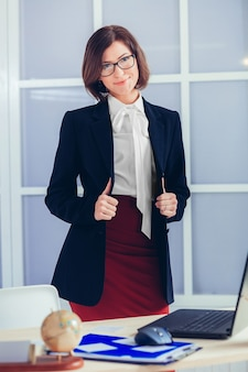 Elegante geschäftsfrau in gläsern im büro.