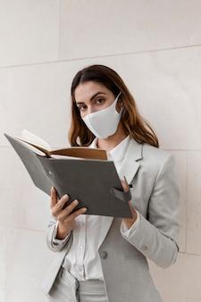 Elegante geschäftsfrau mit maske und agenda