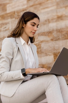 Elegante geschäftsfrau mit smartwatch, die am laptop arbeitet