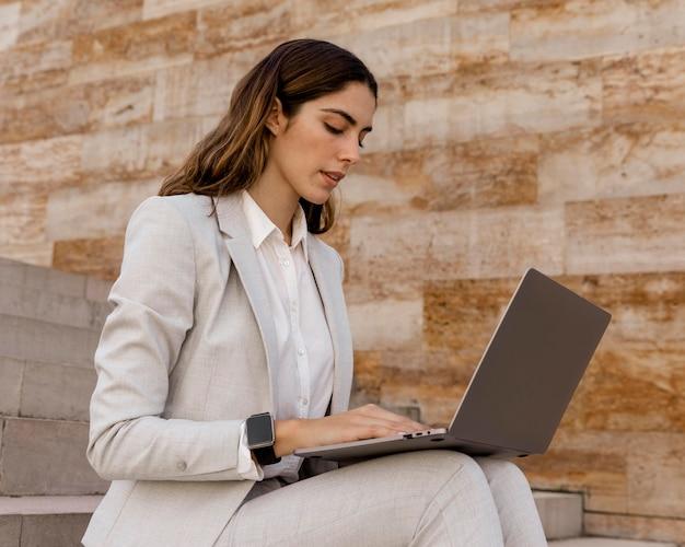 Elegante geschäftsfrau mit smartwatch, die an laptop im freien arbeitet