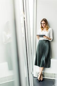 Elegante Geschäftsfrau, die im Büro mit digitaler Tablette steht