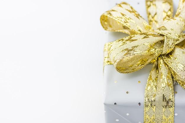 Elegante geschenkbox in grauem silberpapier mit polka dots golden ribbon.