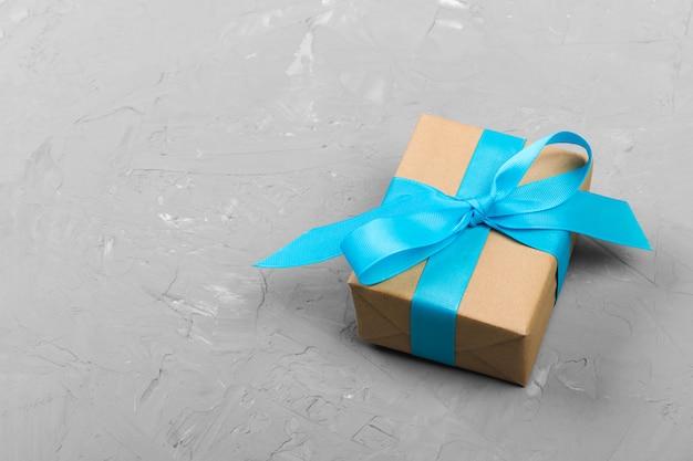 Elegante geschenkbox mit blauem bogen auf grauem hintergrund