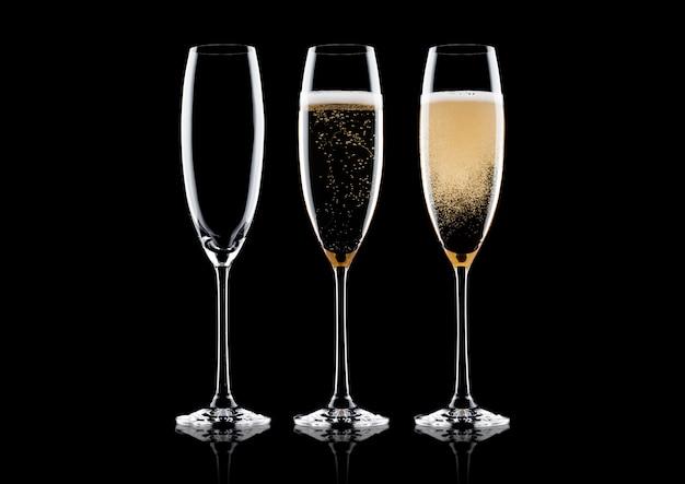 Elegante gläser gelber champagner mit blasen auf schwarzem hintergrund mit reflexion