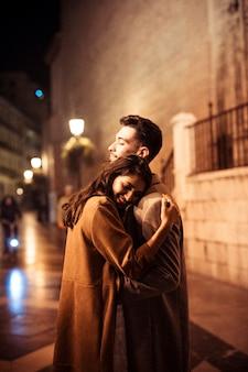 Elegante glückliche frau, die mit jungem mann auf promenade nachts umarmt